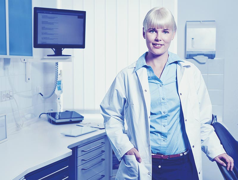 lächelnde Krankenschwester in Behandlungsraum